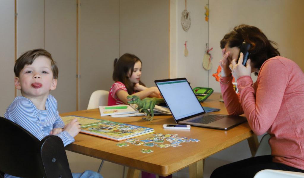 Frau arbeitet zu Hause während Kinder spielen