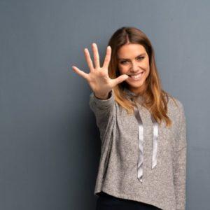 Frau zeigt alle fünf Finger einer Hand