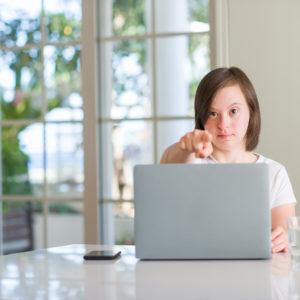 Frau mit Handicap arbeitet am Laptop.