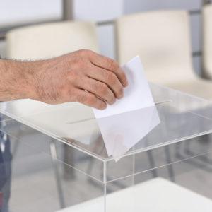 Stimmzettel wird in Wahlurne geworfen.